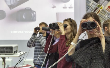 unrecognized: KIEV, UKRAINE - OCTOBER 09, 2016: Unrecognized visitors testing binoculars on Canon booth during CEE 2016, the largest electronics trade show of Ukraine in KyivExpoPlaza EC.