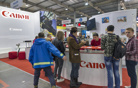 KIEV, UKRAINE - OCTOBER 09, 2016: Unrecognized visitors testing professional photographic cameras on Canon booth during CEE 2016, the largest electronics trade show of Ukraine in KyivExpoPlaza EC.