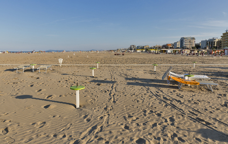 RIMINI, ITALY - SEPTEMBER 24, 2016: Unrecognized people on sandy city beach. Located on the Adriatic Sea it is one of the most famous seaside resorts in Europe, thanks to its 15 km long sandy beach.
