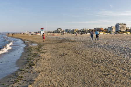 RIMINI, ITALY - SEPTEMBER 24, 2016: Unrecognized people walk along sandy city beach. Located on the Adriatic Sea it is one of the most famous seaside resorts in Europe, thanks to its 15 km sandy beach Editorial