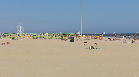 RIMINI, ITALY - SEPTEMBER 24, 2016: Unrecognized people have a rest on city beach. Located on the Adriatic Sea it is one of the most famous seaside resorts in Europe, thanks to its 15 km sandy beach.