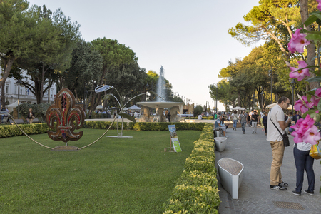 RIMINI, ITALY - SEPTEMBER 24, 2016: Unrecognized people walk in Federico Fellini Park with Fountain of Four horses. Rimini is one of the most famous Adriatic Sea resorts in Europe thanks to its 15 km long sandy beach.