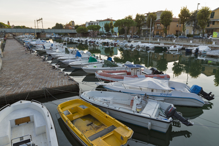 RIMINI, ITALY - SEPTEMBER 24, 2016: Motor boats moored in Channel port at sunset. Rimini is one of the most famous Adriatic Sea resorts in Europe thanks to its 15 km long sandy beach.