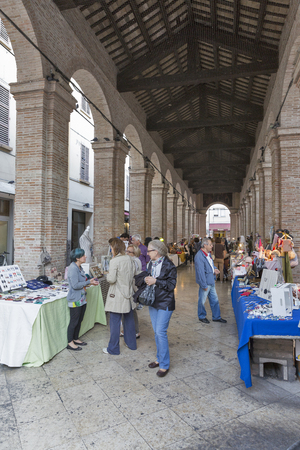 million fish: RIMINI, ITALY - SEPTEMBER 25, 2016: Unrecognized people visit souvenirs market in old fish market gallery on the central city square Piazza Cavour. More than 2 million people visit Rimini every year.