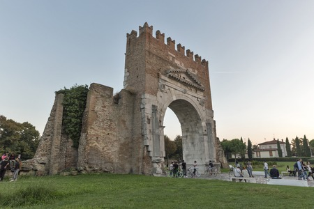 archways: RIMINI, ITALY - SEPTEMBER 25, 2016: People walk in front of Arch of Augustus, ancient romanesque gate of the city - historical Italian landmark, the most ancient Roman arch that still stands intact. Editorial