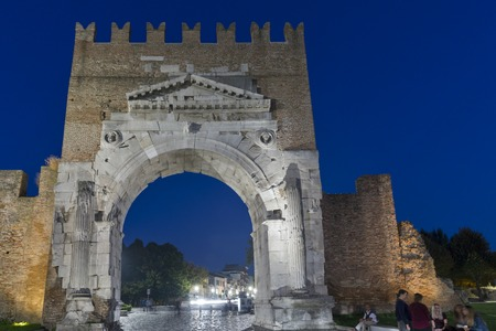 RIMINI, ITALY - SEPTEMBER 25, 2016: Arch of Augustus and 20th September 1870 Street at night. Ancient romanesque gate of city - historical landmark, most ancient roman arch that still stands intact. Editorial