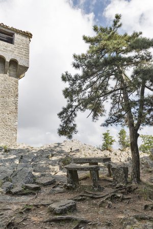 Place for rest on Titano mountain with stone table and bench under the pine close to Castello della Cesta or Cesta fortress, one of three fortress of San Marino. Stock Photo