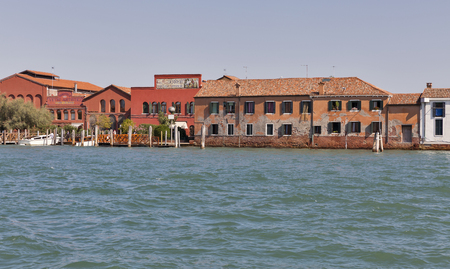 ducale: MURANO, ITALY - SEPTEMBER 22, 2016: Famous Ducale glass making factory facade on the shore of S. Giovanni canal. Murano is a series of islands linked by bridges in the Venetian Lagoon, northern Italy.