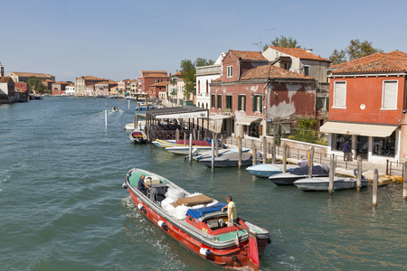 angeli: MURANO, ITALY - SEPTEMBER 22, 2016: People are sailing on motorboat along Canal degli Angeli or Angels Canal. Murano is a group of islands linked by bridges in the Venetian Lagoon, northern Italy.