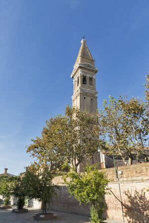 The famous leaning campanile of San Martino church on the island of Burano, Venice, Italy, a popular tourist attraction.
