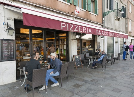 cupido: VENICE, ITALY - SEPTEMBER 22, 2016: Unrecognized people have a rest in pizzeria snack bar Cupido. Venice is situated across a group of 117 islands that are separated by canals and linked by bridges.