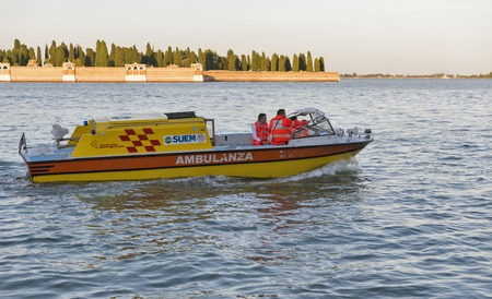 boat crew: VENICE, ITALY - SEPTEMBER 22, 2016: Ambulance motor boat crew sails in Venice lagoon with San Michele cemetery at sunset. Venice situated across 117 islands separated by canals and linked by bridges.