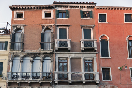 canal house: Ancient house facade on the Grand Canal shore at sunset in Venice, Italy.
