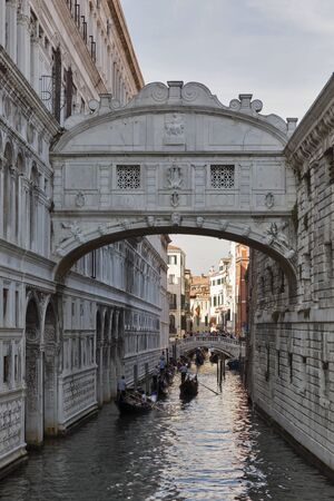 VENICE, ITALY - SEPTEMBER 23, 2016: Unrecognized people travel by gondolas in canal and under the Bridge of Sighs at Doges Palace. Venice is situated across 117 islands that are separated by canals.