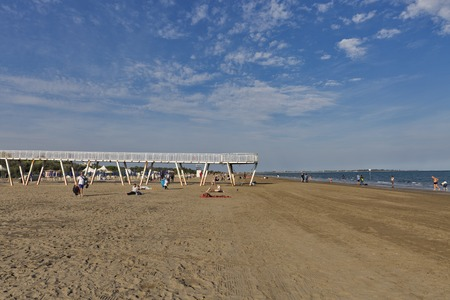 lido: LIDO, ITALY - SEPTEMBER 23, 2016: Unrecognized people have a rest and walk along sandy beach. Lido is an island known for its 11 km long sandbar. Venice Film Festival takes place here every September. Editorial