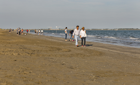 LIDO, ITALY - SEPTEMBER 23, 2016: Unrecognized people have a rest and walk along sandy beach. Lido is an island known for its 11 km long sandbar. Venice Film Festival takes place here every September. Editöryel