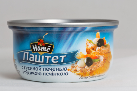 KIEV, UKRAINE - AUGUST 13, 2016: Pate with goose liver Hame tin can with signs in Ukrainian and Russian on white background closeup. Hame is Czech food company, it produce durable and chilled food. Editorial
