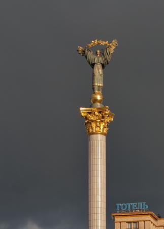 angel de la independencia: KIEV, Ucrania - 05 de abril de 2015: monumento de la independencia en el centro de Kiev contra el cielo tormentoso. Esta es una estatua de un ángel hecho de cobre y oro colocado en un alto pilar en el centro de Kiev. Editorial