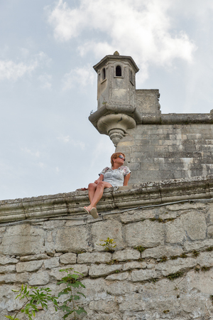 Tanned middle aged caucasian woman in sunglasses sitting in front of watch tower of ruined old Pidhirtsi Castle. It is a residential castle located in the village of Pidhirtsi in Lviv province, Western Ukraine.