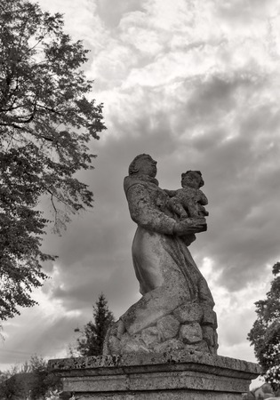 Park statue of St. Joseph baroque Roman Catholic church in black and white against dramatic sky in Pidhirtsi, Ukraine. Pidhirtsi village is located in Lviv province, Western Ukraine.