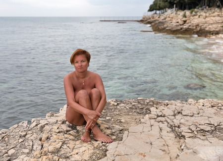 Naked tanned middle aged caucasian woman sitting on the sea rocky beach. Istria, Croatia. Stock Photo