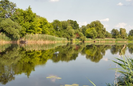 Quiet Ros river in summer with trees reflection, Ukraine