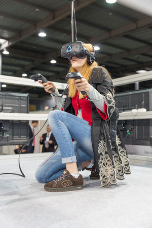 KIEV, UKRAINE - APRIL 7, 2017: Young girl use Nomi Vive virtual reality game glasses and hand controllers at International Trade Show of Electric and Hybrid Vehicles Plug-In Ukraine in KyivExpoPlaza. Editorial