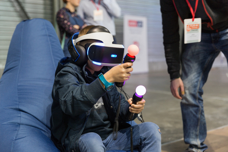 KIEV, UKRAINE - APRIL 07, 2017: Boy use virtual reality game glasses and hand controllers at 2nd International Trade Show of Electric and Hybrid Vehicles Plug-In Ukraine in KyivExpoPlaza venue. Editorial