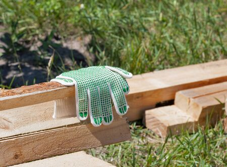 Construction wooden cottage. Processed pine bars with new work gloves outdoor closeup.