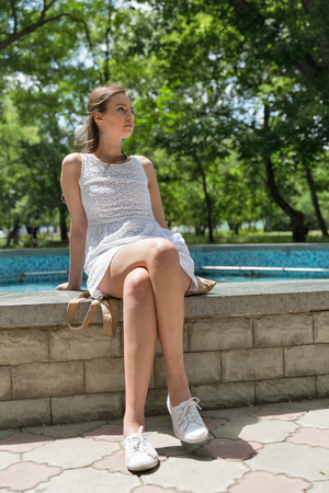 Young beautiful caucasian girl in a short white dress sit with crossed legs near fountain in city park