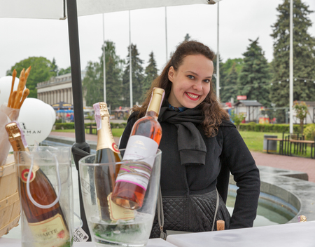 KIEV, UKRAINE - MAY 13, 2017: Unrecognized woman presenter works on booth during Kyiv Food and Wine Festival in National Expocenter, a permanent multi-purpose complex in the Teremky neighborhood.
