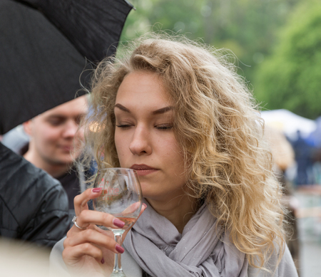 KIEV, UKRAINE - MAY 13, 2017: Unrecognized young woman taste wine during Kyiv Food and Wine Festival in National Expocenter, a permanent multi-purpose exhibition complex in the Teremky neighborhood.