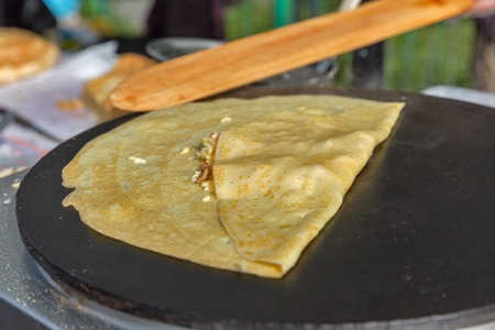 roasting pan: Making pancake with filling on frying electric stove outdoor closeup