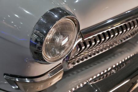 rusty car: Retro headlight of white vintage car closeup