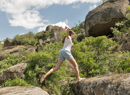 Young caucasian beautiful fitness woman running barefoot at mountain rocks Stock Photo