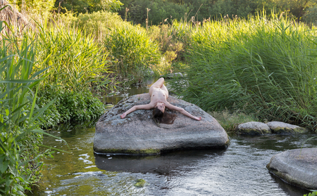Beautiful young girl naked lies with arms outstretched on big river stone at sunny day