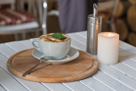 mocca: Coffee cup on bar table and romantic candles closeup