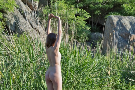 Beautiful young girl naked standing back half turn to the camera on big river stone at sunny morning