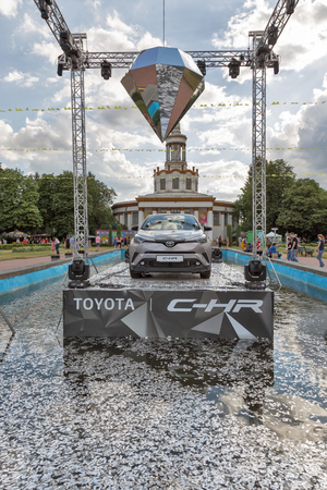 chr: KIEV, UKRAINE - JULY 02, 2017: Promotional booth with new Toyota C-HR modern design hybrid crossover in the fountain at the Atlas Weekend Festival in National Expocenter. Editorial