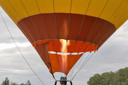 Hot air from a gas burner fills the dome of the balloon closeup