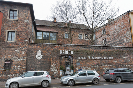 KRAKOW, POLAND - JANUARY 13, 2017: Cars parked in front of Hamsa Israeli restaurant facade in Kazimierz Jewish district. Krakow is the second largest and one of the oldest cities in Poland.