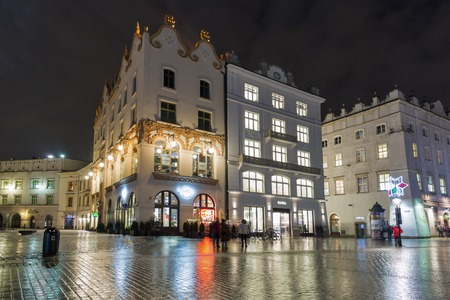KRAKOW, POLAND - JANUARY 12, 2017: Unrecognized people walk along Hard Rock Cafe on Main Market square in old town at night. Krakow is the second largest and one of the oldest cities in Poland. Editorial