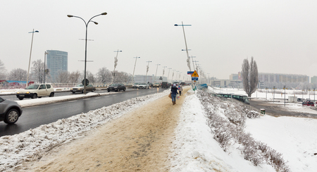 RZESZOW, POLAND - JANUARY 17, 2017: Unrecognized people walk along Castle bridge over Wislok river in winter. Rzeszow is the largest city in southeastern Poland, it is located on Wislok River in Sandomierz Basin.
