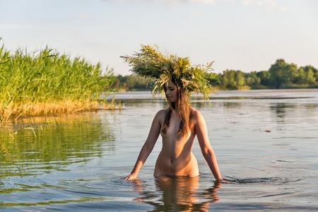 花の花輪で美しい白人若い裸の女性には、水の楽しさがあります。イヴァンクパーラ休日のお祝い。
