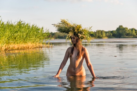 Beautiful caucasian young naked woman with wreath of flowers have fun in water. Ivan Kupala holiday celebration. Stock fotó - 84421105
