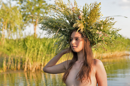 Beautiful caucasian young naked woman with wreath of flowers have fun in water. Ivan Kupala holiday celebration.