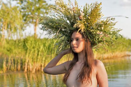 De mooie Kaukasische jonge naakte vrouw met kroon van bloemen heeft pret in water. Ivan Kupala vakantie vieren.