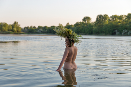 Beautiful caucasian young woman with wreath of flowers have fun in water. Ivan Kupala holiday celebration.