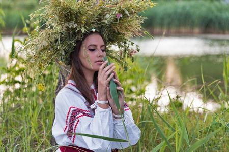 Bella giovane ragazza caucasica in camicia nazionale ricamo ucraino e corona di fiori selvatici ritratto. Festa di Ivan Kupala in Ucraina. Archivio Fotografico - 84630389