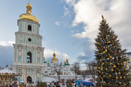 KIEV, UKRAINE - JANUARY 03, 2017: People visit Christmas fair in front of Saint Sophia Cathedral bell tower. Saint Sophia Cathedral is an outstanding architectural monument of Kievan Rus.
